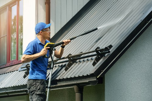 A metal roof maintenance worker services a metal roof.